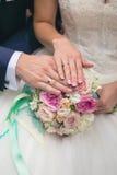 Руки groom и невесты на букете свадьбы Стоковые Фото