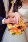 Руки groom и невесты на букете свадьбы Стоковые Фотографии RF