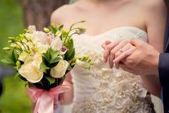 Руки groom и невесты на букете свадьбы Стоковые Изображения RF