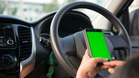 руки 4K женщины используя используя smartphone с зеленым монитором экрана на интерьере автомобиля SUV для передвижной технологии  акции видеоматериалы