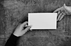 Руки Monochrome фото мужские держа белый чистый лист бумаги Стоковая Фотография