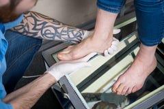 Руки orthopedist доктора молодого человека проводят диагностики, испытание ноги ноги женщины, для изготовления индивидуала, или стоковые изображения rf