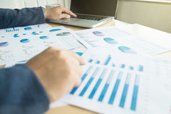 Руки ` s бизнесмена на работе с финансовым планом и компьтер-книжкой Стоковые Изображения