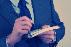 Руки ` s бизнесмена с ручкой в его руке Стоковая Фотография