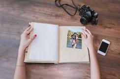 Руки ` s девушки держат альбом для фото с камерой и phon Стоковое фото RF