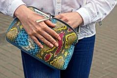 Руки ` s девушки держат яркую покрашенную сумку Стоковые Изображения