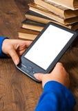 Руки ` s девушки держат EBook на мобильном устройстве над кучей старой бумажной книги с пустым белым экраном на деревянной предпо Стоковые Изображения
