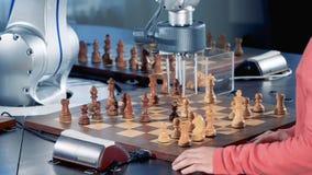 Руки ` s девушки и robotized рука двигают шахматные фигуры в поворотах акции видеоматериалы