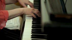 Руки ` s девушки на клавиатуре рояля Девушка играет рояль, конец вверх по роялю Руки на белых ключах рояля Стоковое Изображение