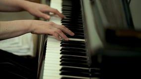 Руки ` s девушки на клавиатуре рояля Девушка играет рояль, конец вверх по роялю Руки на белых ключах рояля Стоковые Изображения RF