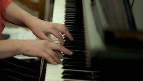 Руки ` s девушки на клавиатуре рояля Девушка играет рояль, конец вверх по роялю Руки на белых ключах рояля Стоковое фото RF