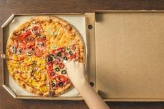 Руки ` s девушки отрезали огромную пиццу в коробке 4 пиццы в одной Стоковое фото RF