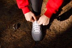 Руки ` s девушки связывают шнурки в лесе во время тренировки Стоковое Изображение RF