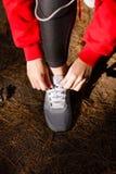 Руки ` s девушки связывают шнурки в лесе во время тренировки Стоковое Изображение