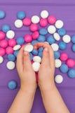 Руки ` s детей держа покрашенные конфеты Стоковое Изображение RF