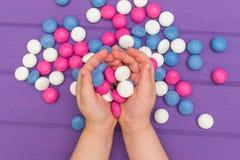 Руки ` s детей держа покрашенные конфеты Стоковая Фотография