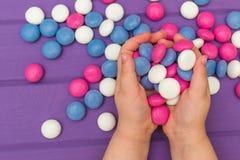 Руки ` s детей держа покрашенные конфеты Стоковые Изображения