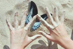 Руки ` s детей для того чтобы уловить голубую бабочку Стоковые Изображения
