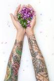 Руки ` s девушки с татуировками и цветками Стоковое Фото