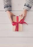 Руки ` s женщины дают подарок рождества в присутствующей коробке Стоковое Изображение