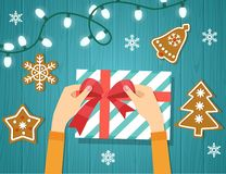 Руки ` s женщины дают обернутый настоящий момент праздника рождества handmade в бумаге с красной лентой ПеченьеGingerbreadДере бесплатная иллюстрация