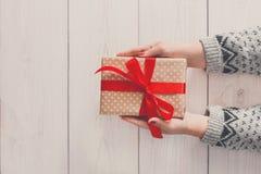 Руки ` s женщины дают подарок рождества в присутствующей коробке Стоковая Фотография RF