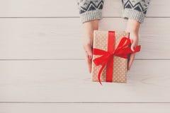 Руки ` s женщины дают подарок рождества в присутствующей коробке Стоковое Изображение RF