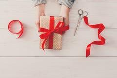 Руки ` s женщины дают подарок рождества в присутствующей коробке Стоковое фото RF