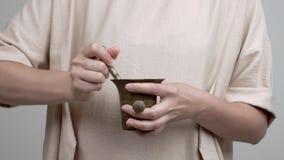 Руки ` s женщины держат миномет и пестик Она добавляет лепестки розы и начинает mortaring они нежно сток-видео