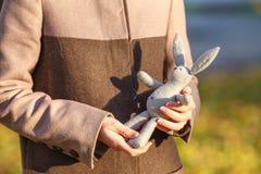 Руки ` s женщины держа кролика игрушки Стоковое фото RF
