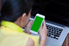 Руки ` s женщины используя сотовый телефон и портативный компьютер на древесине пола Стоковое Изображение RF
