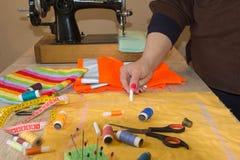 Руки ` s женщины рисуя картину на ярком материале на ее рабочем месте в магазине портноя Стоковые Фото