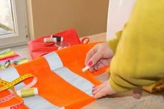 Руки ` s женщины рисуя картину на ярком материале на ее рабочем месте в магазине портноя Стоковое Фото