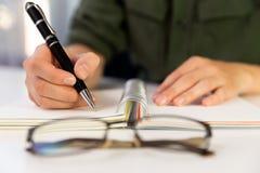 Руки ` s женщины с сочинительством ручки на тетради Современный стол офиса стоковые фотографии rf