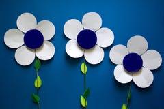 Руки ` s женщин держа бумажные цветки с металлическим cream контейнером опарника на предпосылке голубой бумаги Стоковое Фото