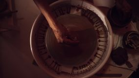 Руки ` s женщин работают на колесе ` s гончара формируя длинный тонкий глиняный горшок сток-видео