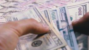 Руки ` s людей держат кучу американских долларов на фоне вращая денег акции видеоматериалы