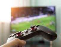 Руки ` s людей с кнюппелем на предпосылке ТВ, играя футбол, конец-вверх стоковые фотографии rf