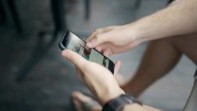Руки ` s людей с smartphone Парень смотрит на телефоне и перечисляет новости instagram сток-видео