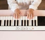 Руки ` s маленькой девочки играя электронный рояль Стоковые Изображения RF