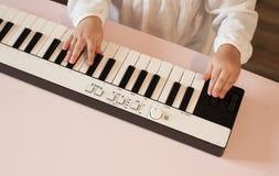 Руки ` s маленькой девочки играя электронный рояль Стоковая Фотография