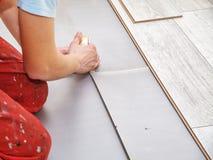 Руки ` s разнорабочего кладя вниз с слоистых доск настила Стоковое Фото