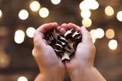 Руки ` s ребенка держа деревянные звезды Стоковая Фотография