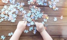 Руки ` s ребенка собирают сложенные головоломки на фоне деревянного стола Стоковые Фото