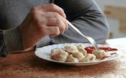 Руки ` s человека крупного плана едят вареники при вилка, кладя их в томатный соус в кухне Стоковое Изображение