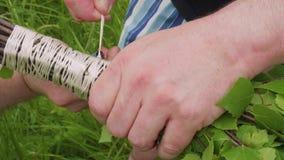 Руки ` s человека связывают ветви березы делая веники для сауны акции видеоматериалы