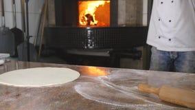 Руки ` s шеф-повара свертывают тесто в пиццу стоковые изображения