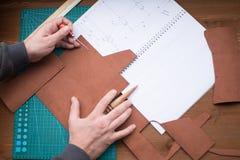 Руки Tanners на работе с шилом, slicker и кожей Выбранный фокус, конец вверх стоковая фотография