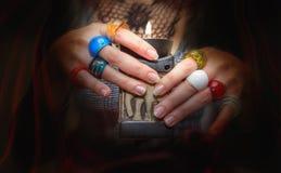 Руки Woman's при много красочных стеклянных колец держа candlelig Стоковые Фото