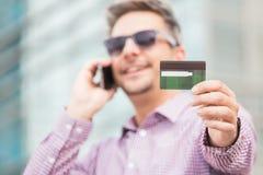 Руководитель бизнеса используя smartphome и показывающ кредитную карточку outdoors стоковые фото